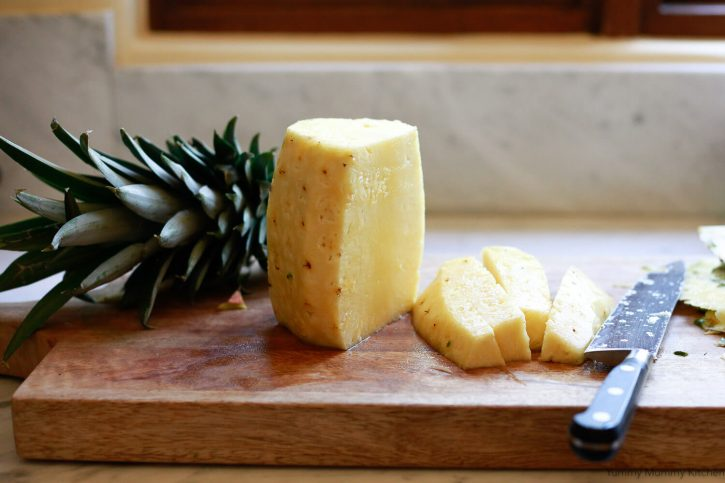 A whole peeled pineapple is cut into spears on a wooden cutting board.