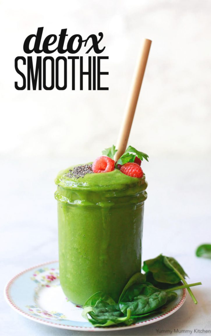 A glass jar filled with a green detox smoothie topped with raspberries and chia seeds. This detox smoothie recipe with spinach is great for weight loss and liver detox.