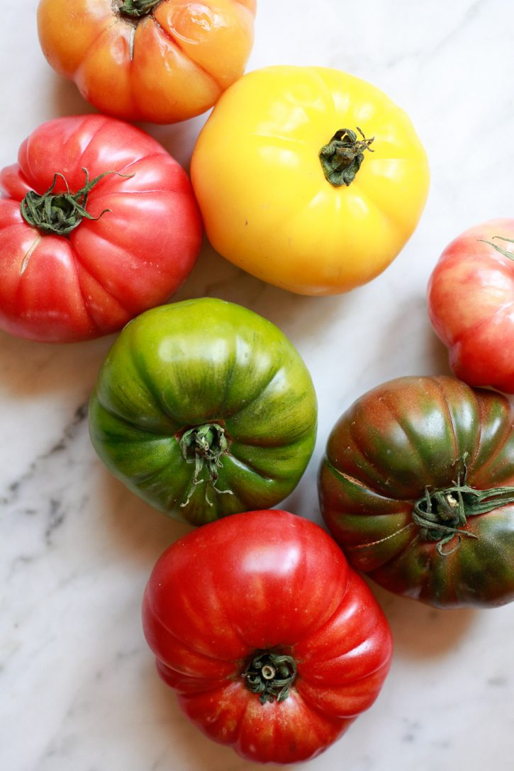 Colorful red, yellow, and green heirloom tomatoes on a marble countertop.
