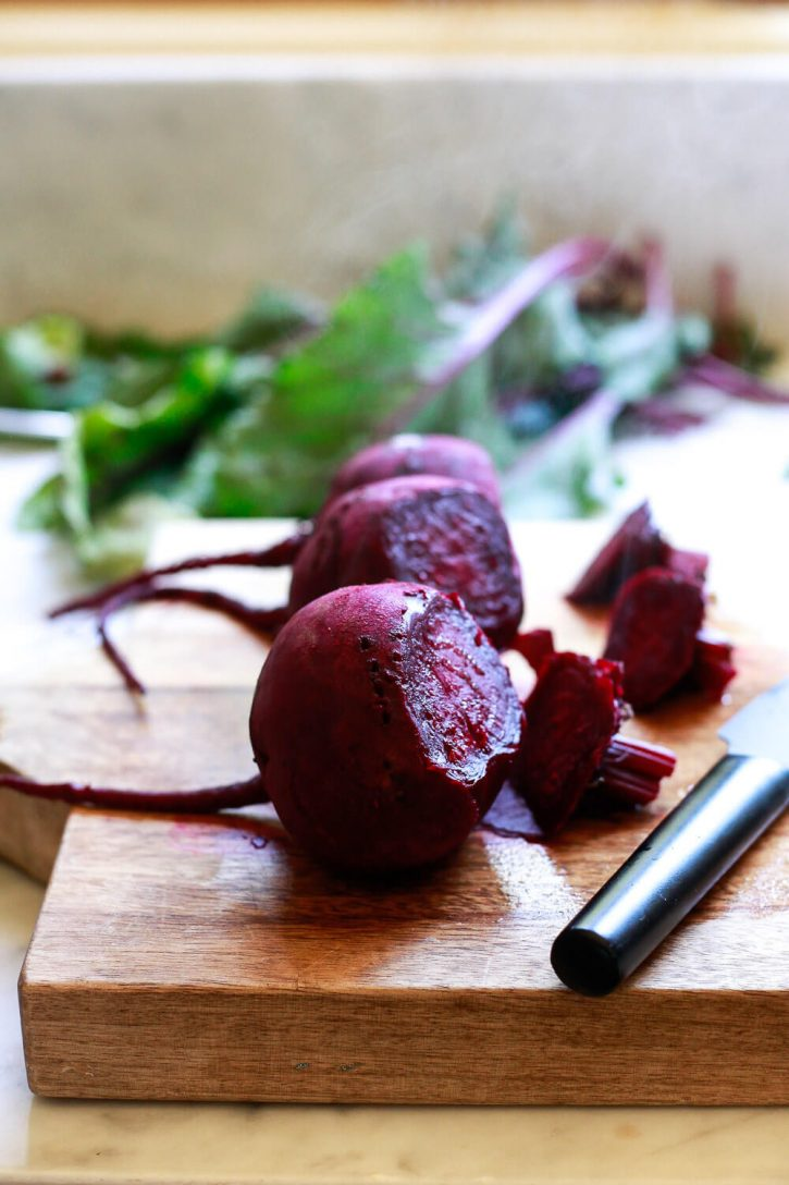 Three cooked beets on a cutting board before being cut into quarters for pickled beets.