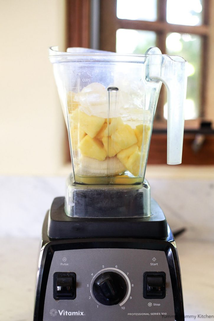 Ingredients for a pineapple smoothie in a Vitamix blender. The healthy vegan pineapple smoothie ingredients are pineapple juice, banana, frozen pineapple, frozen mango, and ice.