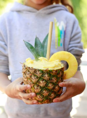 A girl holds a pineapple smoothie in a real pineapple.