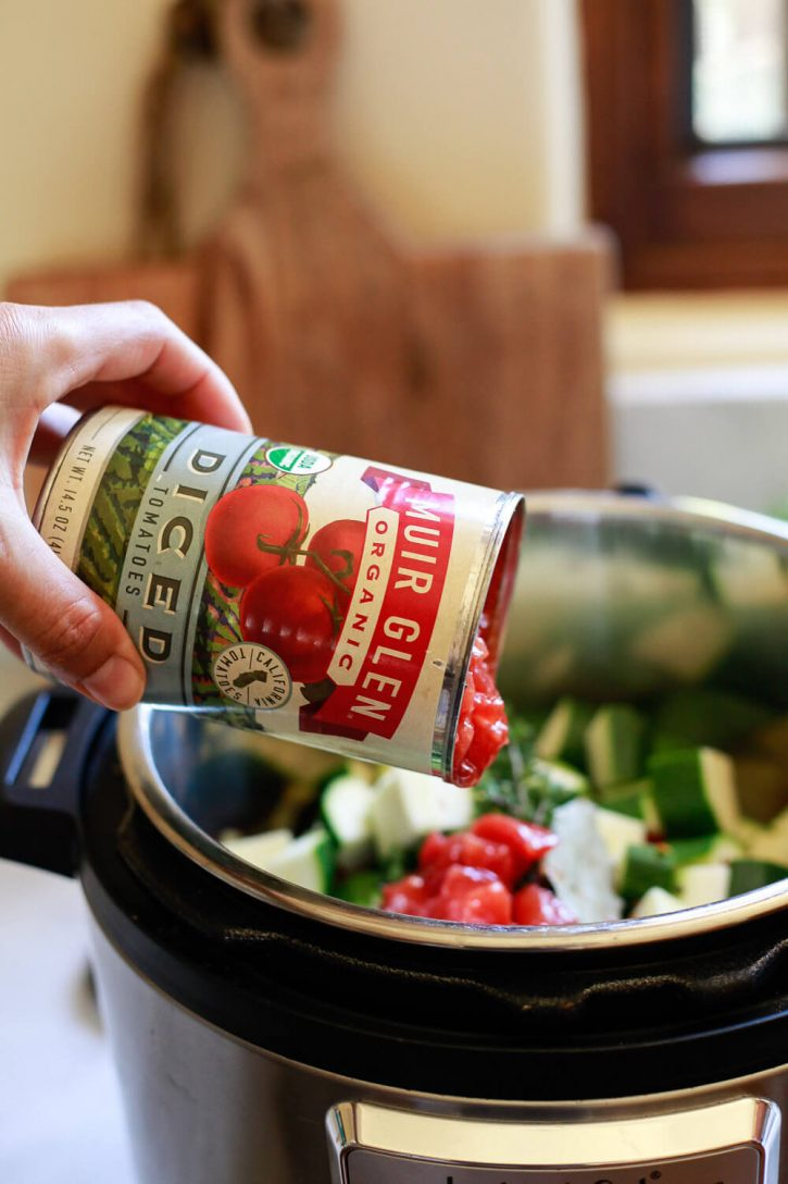 A can of diced tomatoes gets poured into a crock pot or Instant Pot to make ratatouille.