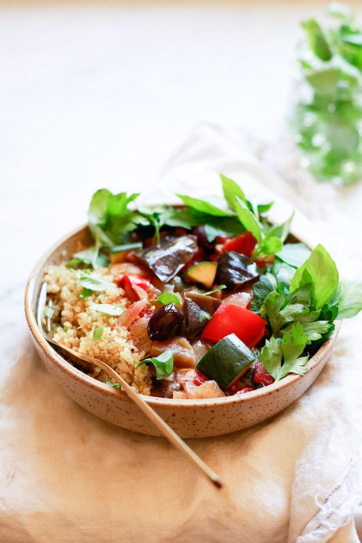 A bowl of ratatouille served with quinoa and fresh basil. The traditional rustic ratatouille can be made in the crock pot slow cooker or Instant Pot pressure cooker.