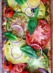 A beautiful vegan pizza with heirloom tomatoes and basil pesto.
