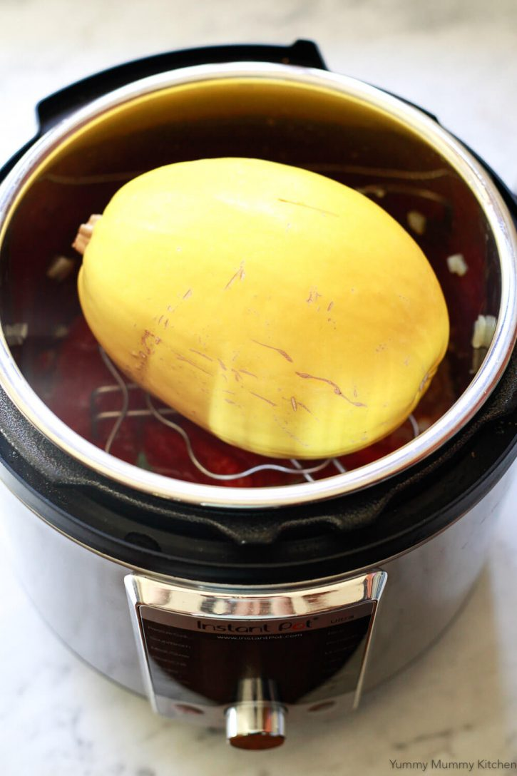 A whole spaghetti squash sits on a trivet on top of homemade spaghetti sauce in an Instant Pot.