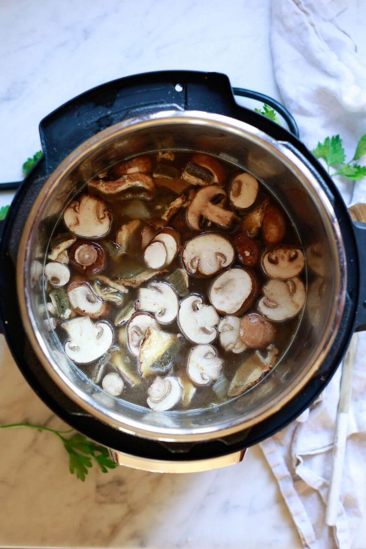 All the ingredients for mushroom risotto are in an Instant Pot ready to cook.