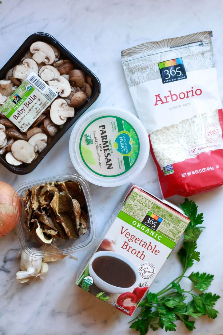 Ingredients for mushroom risotto on a marble countertop. Arborio rice, Parmesan, dried and fresh mushrooms, vegetable broth, onion, and garlic.