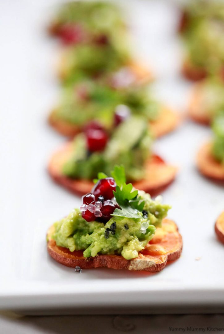 A slice of sweet potato toast (crostini) with avocado, pomegranate, and cilantro. A healthy vegan appetizer recipe.