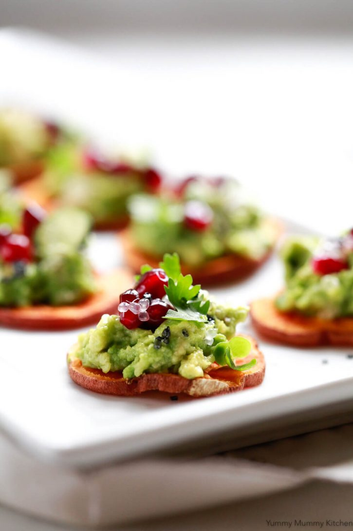 Baked sweet potato slices with avocado, finger lime, and pomegranate are healthy vegan appetizers, holiday appetizers, and sweet potato toast ideas.