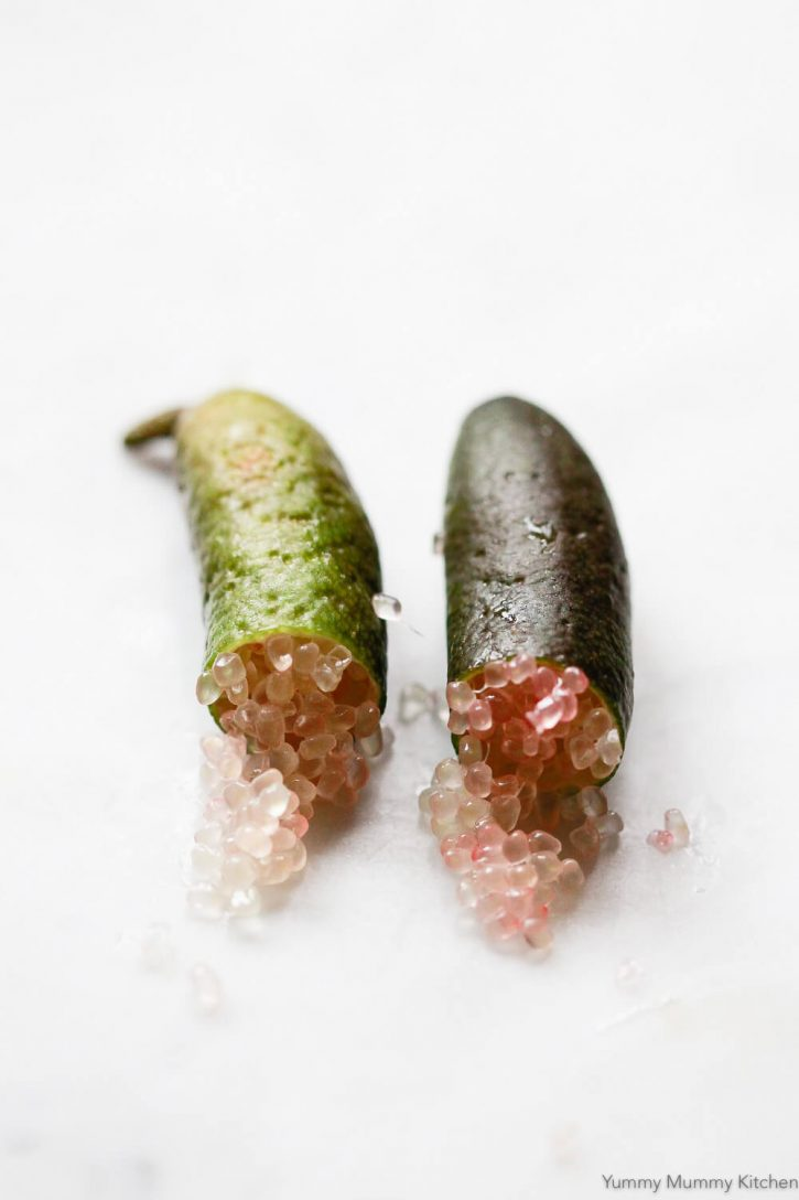 A close-up photo of caviar limes, or finger limes, cut in half with pink lime juice caviar spilling out.