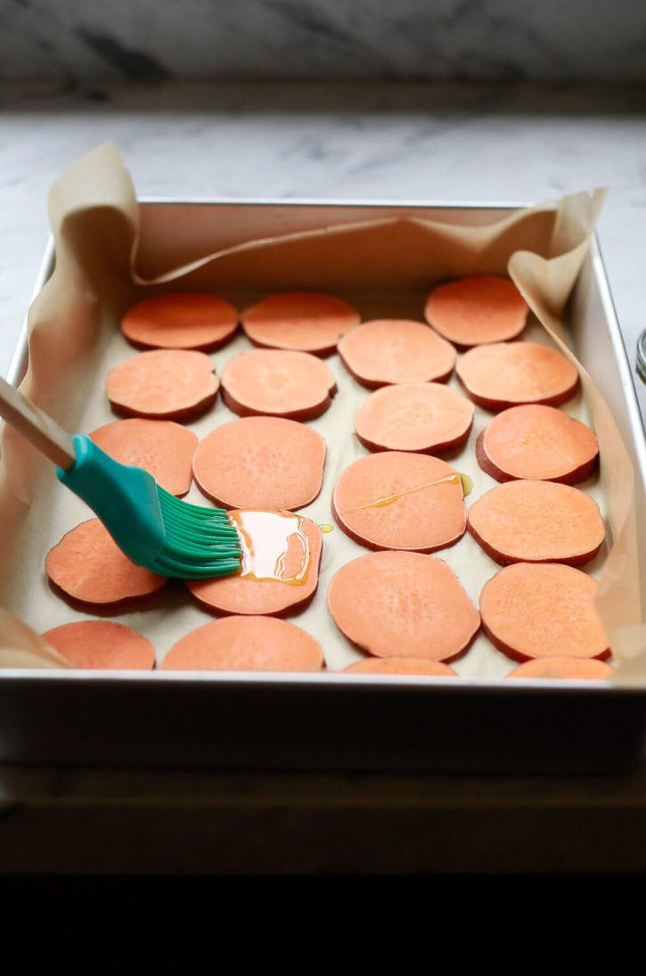 Sweet potato slices are brushed with olive oil before baking into sweet potato crostini, a healthy vegan appetizer.