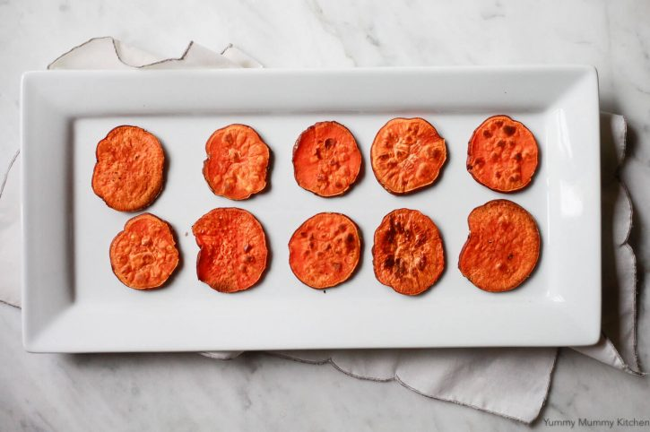 A tray filled with sweet potato toast rounds, or crostini, ready to be topped with avocado.