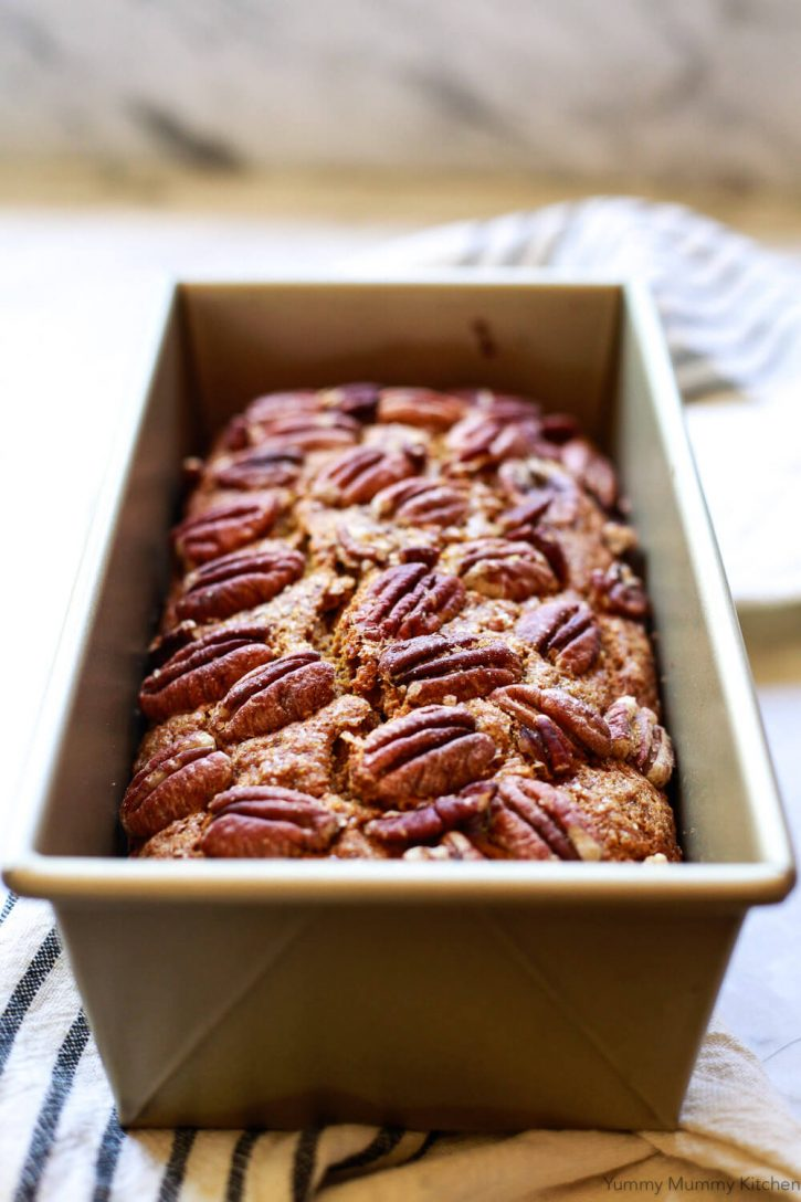 A vegan pumpkin bread loaf topped with pecans on a kitchen counter.