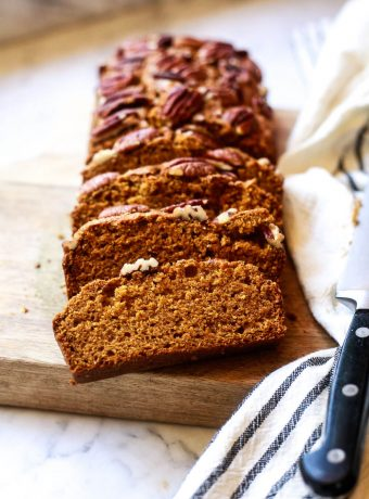 A loaf of sliced vegan pumpkin bread topped with pecans.