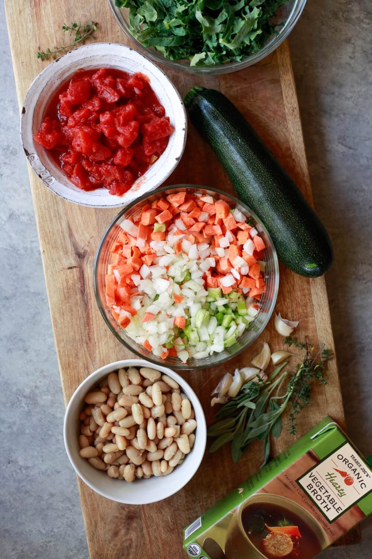 The ingredients for Italian vegetable soup on a cutting board: diced carrots, onion, and celery, diced tomatoes, zucchini, white beans, kale, vegetable broth and herbs.