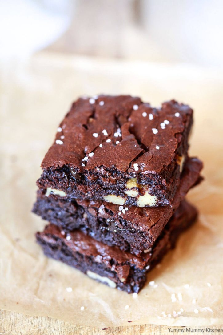 A stack of the best vegan brownies on a sheet of parchment paper. How to make the BEST vegan brownies ever! Easy fudgy vegan brownies with a crackly top! This vegan brownie recipe is dairy free and eggless.