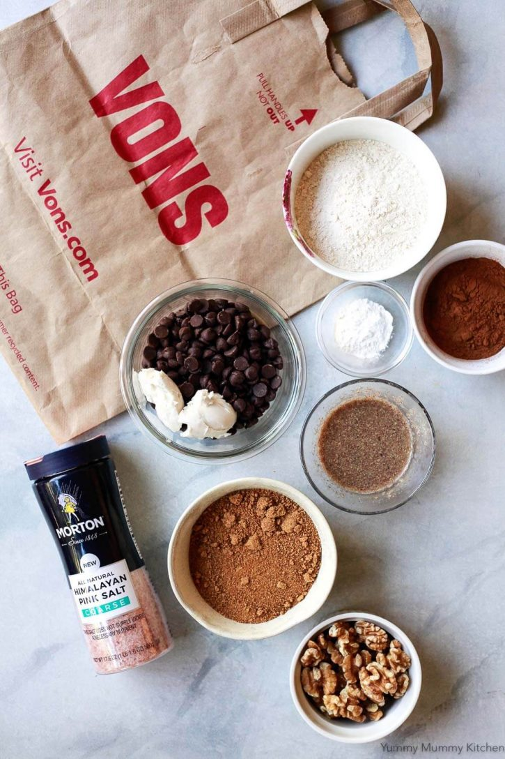 The ingredients for vegan brownies on a countertop include flour, chocolate chips, vegan butter, flax egg, cocoa powder, coconut sugar, and walnuts.