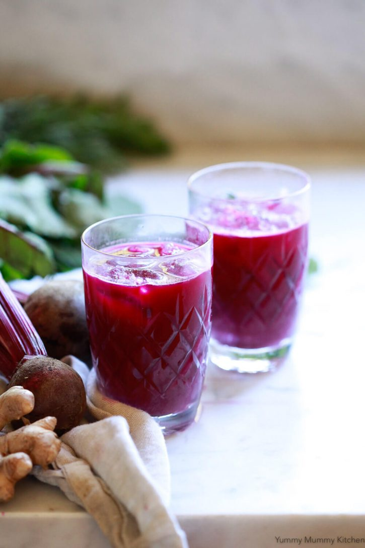 Beautiful vital red detox juice in glasses with ice on a white kitchen counter. Beets and ginger are seen in the background.