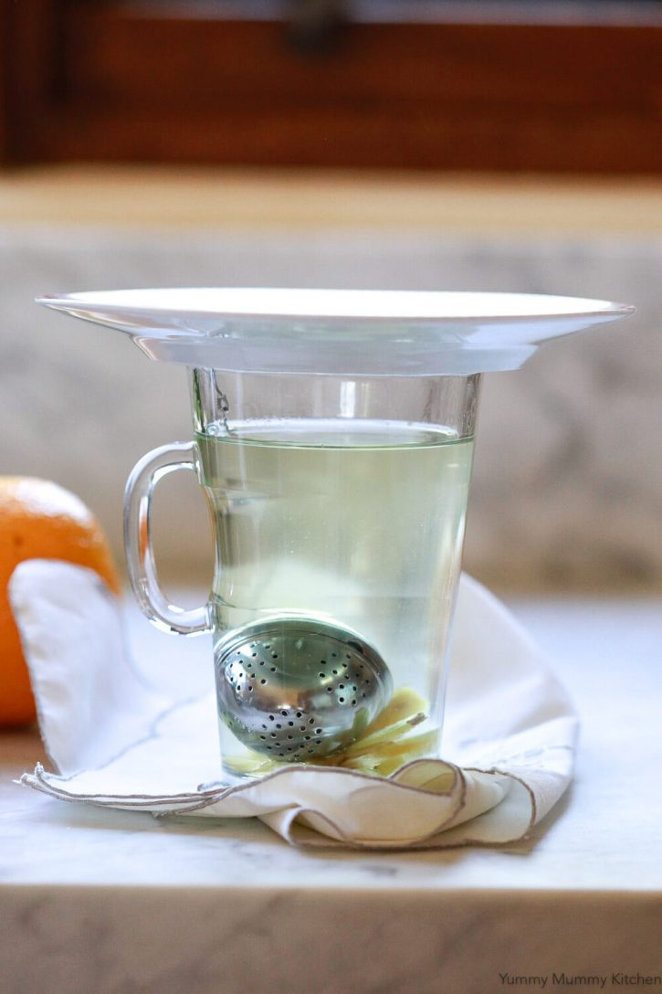 Homemade detox tea steeps in a glass tea cup with ginger at the bottom. The glass is covered with a small saucer to retain heat.