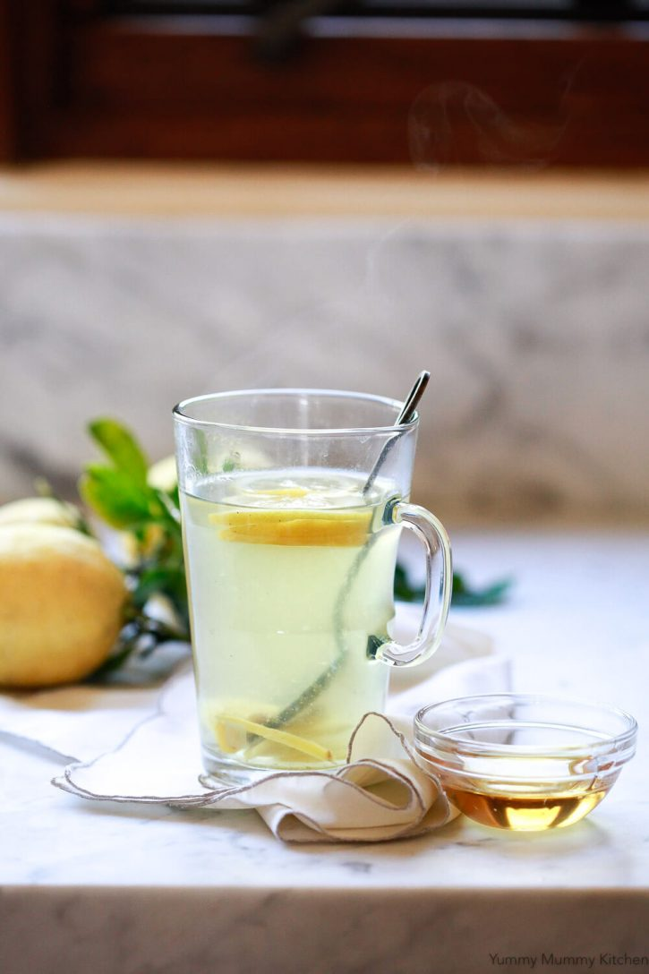 Steam comes off a cut of homemade detox tea with ginger and lemon.