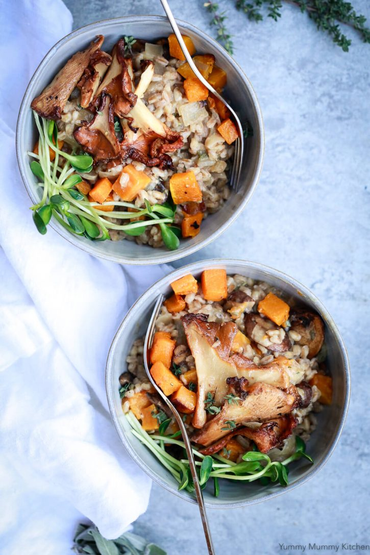Two bowls of creamy mushroom farro risotto, or farrotto, topped with wild mushrooms and roasted butternut squash.