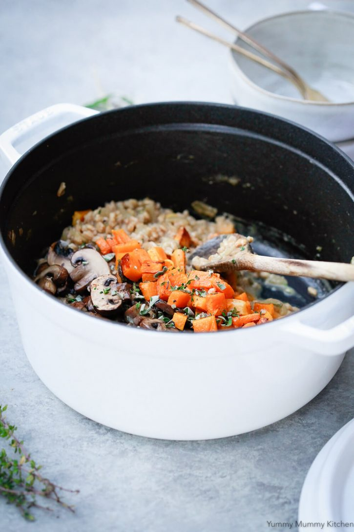 A white Staub pot filled with creamy mushroom farrotto (farro risotto) and topped with sauteed mushrooms and roasted butternut squash.
