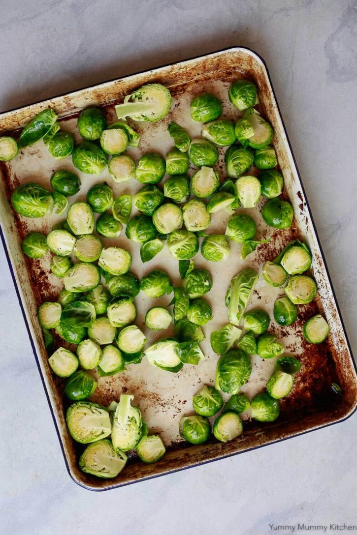 Raw Brussels sprouts on a sheet pan for roasting.