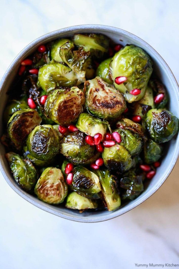 A beautiful photo of crispy roasted Brussels sprouts in a bowl topped with pomegranate arils. This Brussels sprout recipe is a perfect healthy Thanksgiving or Christmas side dish.