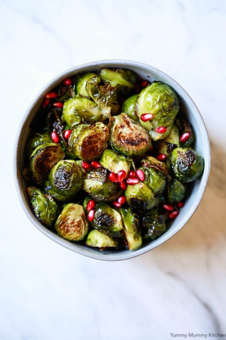 A bowl of oven roasted balsamic Brussels sprouts garnished with pomegranate arils. How to cook Brussels sprouts! Learn all about this wonderful veggie, get plenty of creative Brussels sprouts recipes, and learn to make our favorite roasted balsamic Brussels sprouts. They are a delicious and easy vegetarian, gluten-free side dish for holidays like Thanksgiving and Christmas, or everyday dinners.