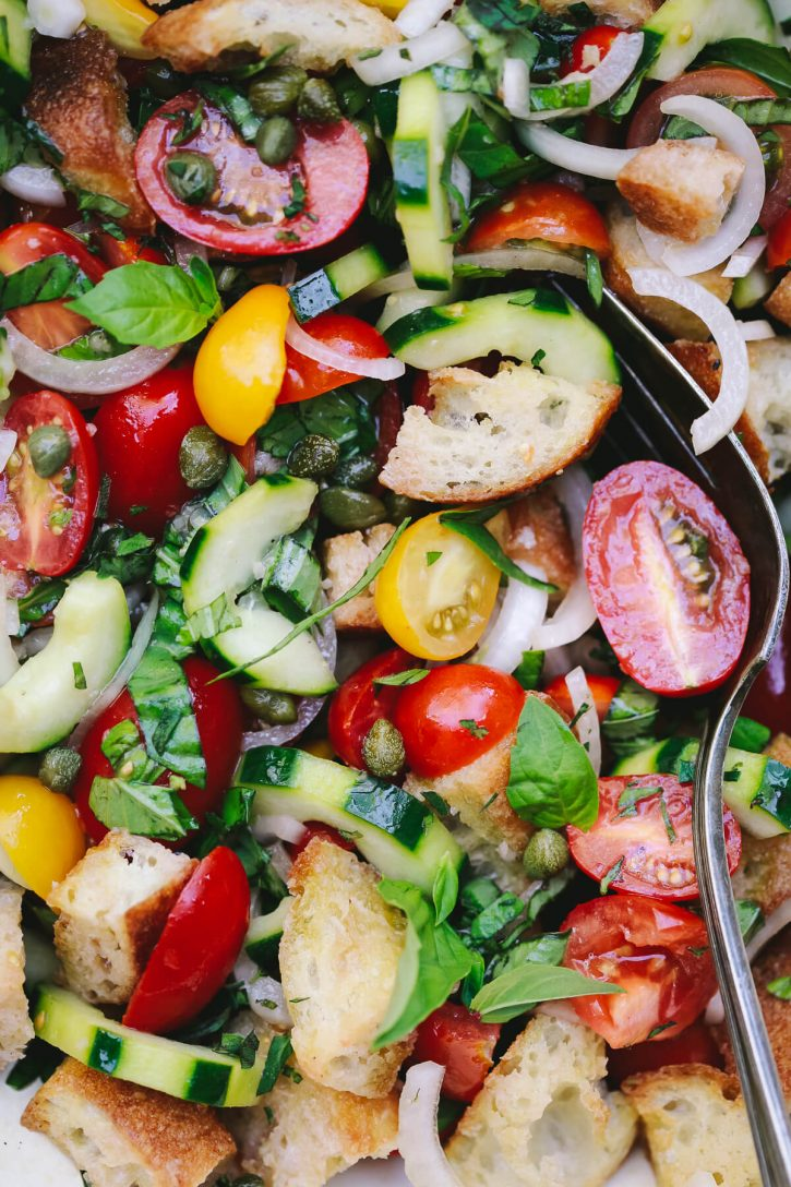 A close-up photograph of panzanella salad. This Italian tomato and bread salad has cucumbers capers, basil, and onions. A beautiful summer salad.