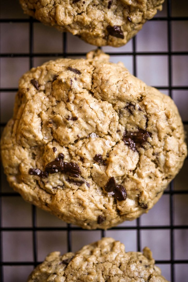 Close-up macro photography of a peanut butter oatmeal cookie with melty dark chocolate chunks and Maldon salt.