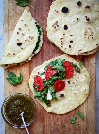 Piadina bread on a cutting board being filled with tomatoes and mozzarella cheese. These are Italian flatbread sandwiches.