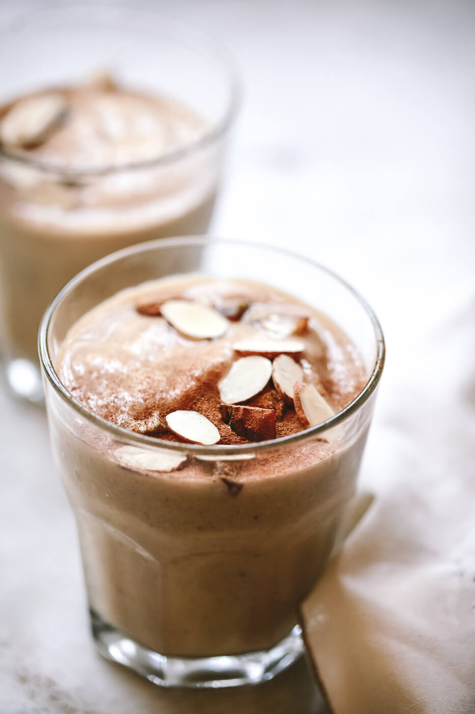 A close-up photo of a homemade healthy date shake in a clear glass. This shake is topped with slivered almonds, chopped Medjool dates, and a dusting of cinnamon.
