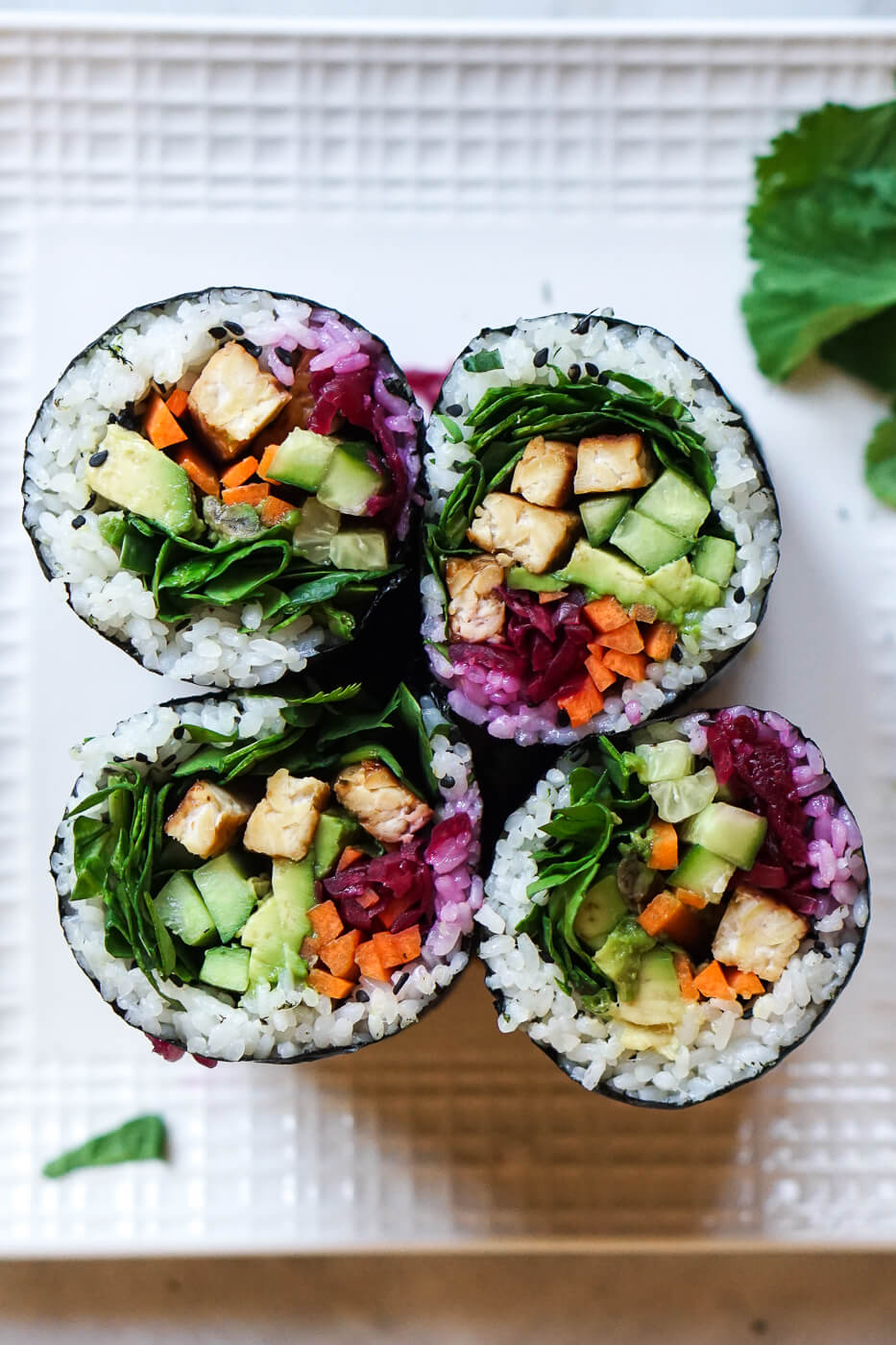 An overhead photo of 4 sushi burritos filled with tempeh, cucumber, carrots, avocado, and more.