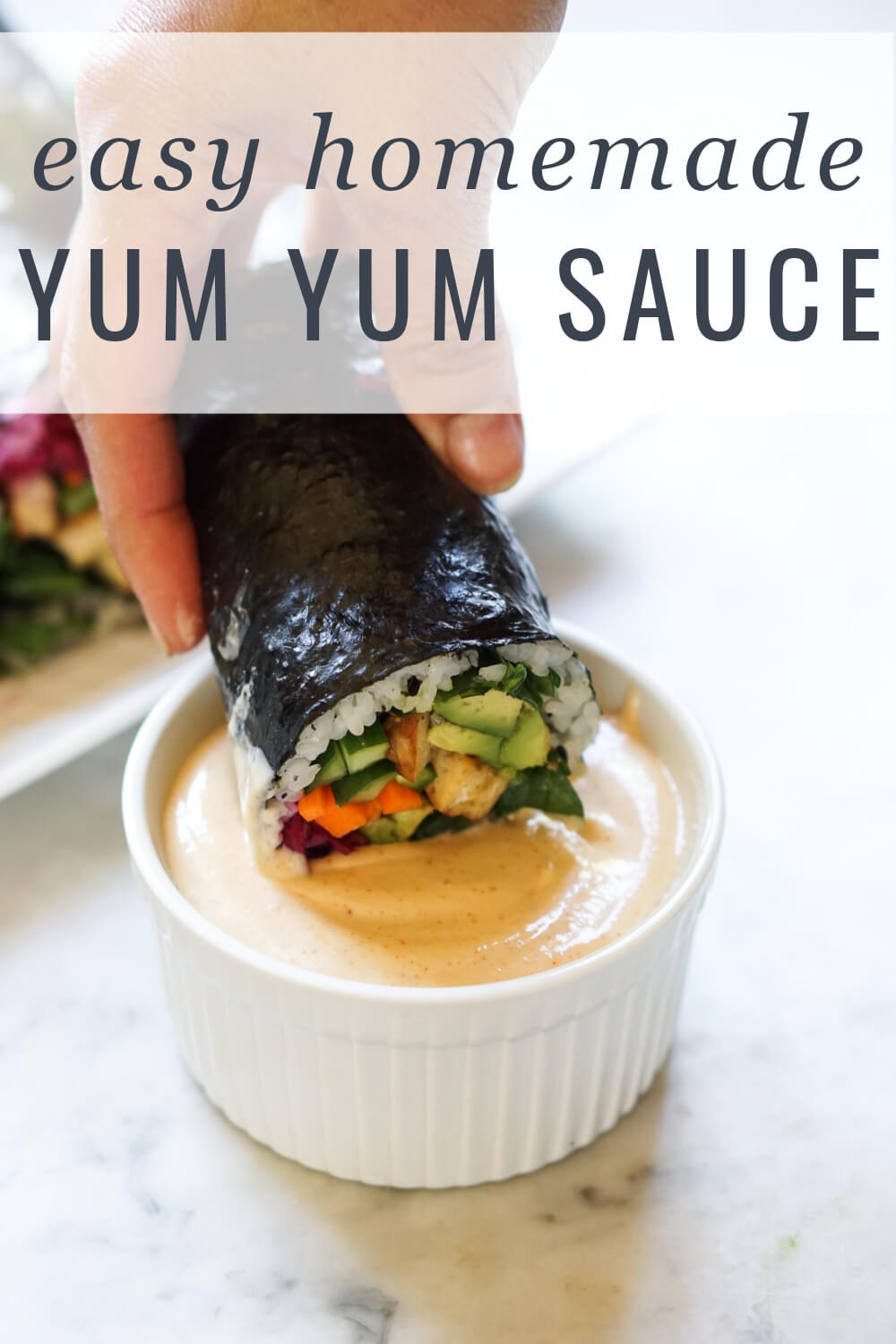 Sushi is dipped into a small white bowl filled with homemade Japanese yum yum sauce just like at Benihana hibachi restaurants!