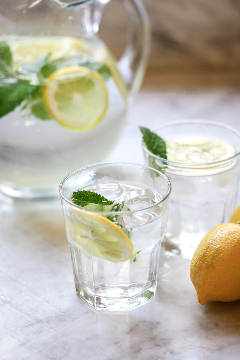 Glasses filled with lemon water garnished with mint on a white marble countertop.