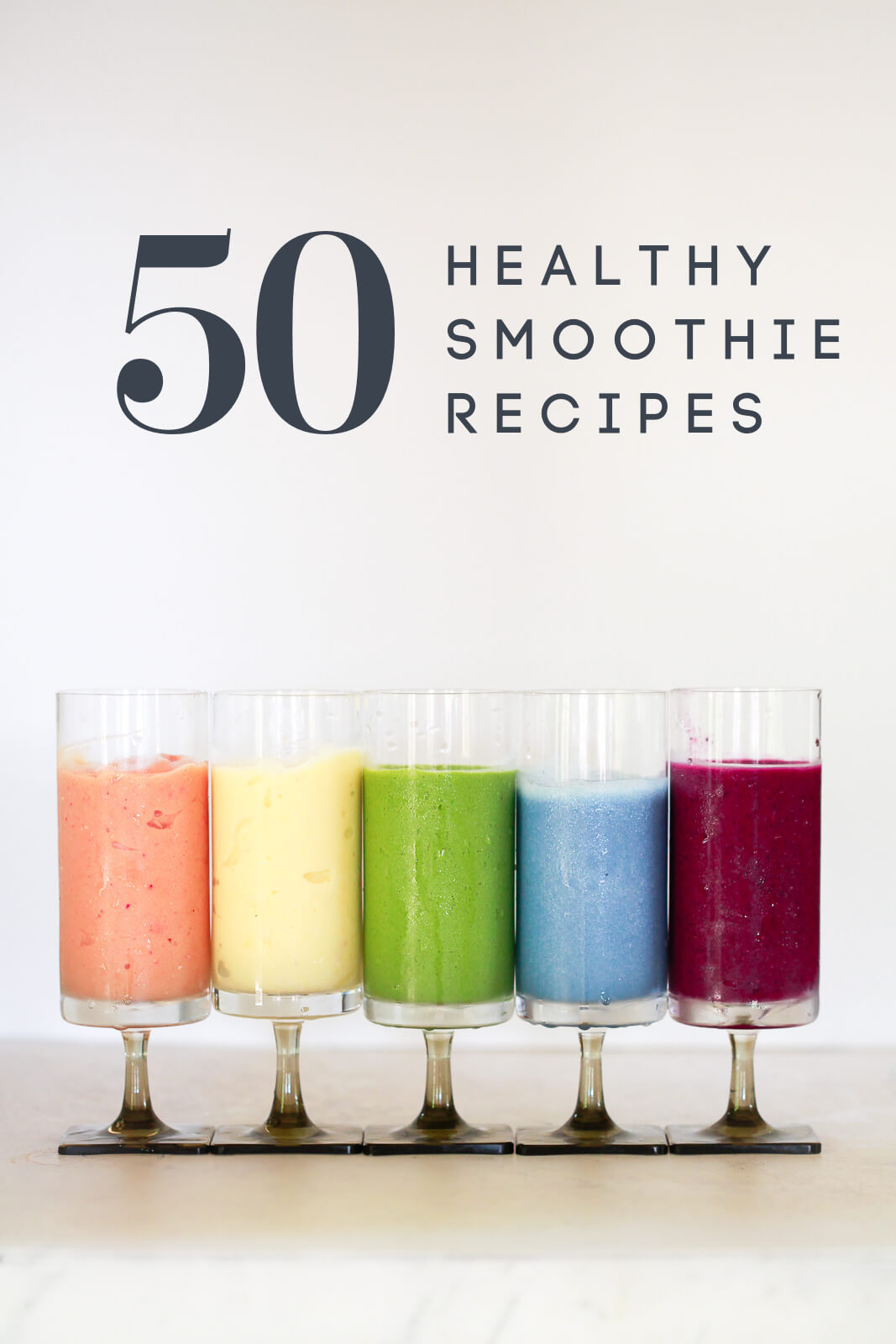 """5 colorful healthy smoothies on a white kitchen counter. Text overlay reads """"50 healthy smoothie recipes"""""""